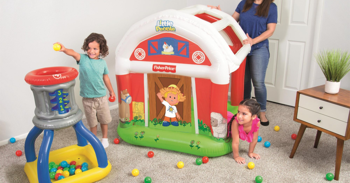 two kids playing in barn ball pit and silo set in living room with mother standing by