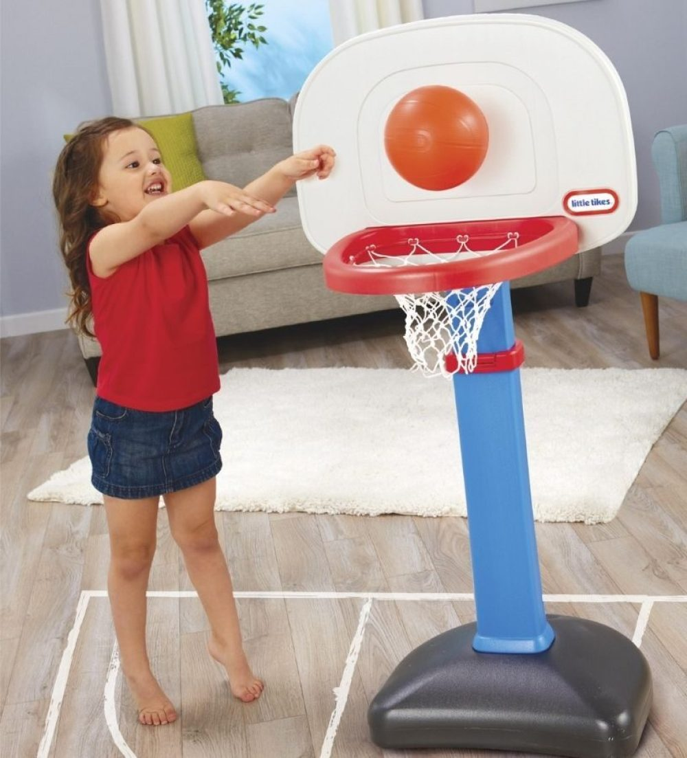 Little girl playing with Little Tikes toy basketball hoop