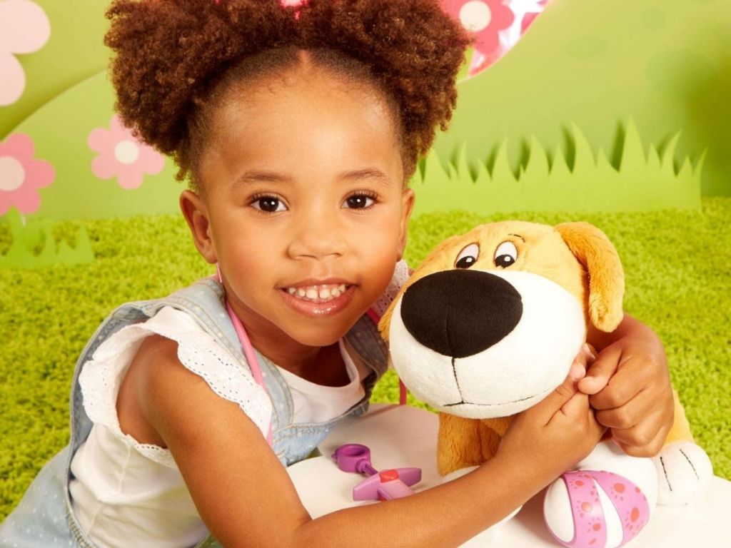 Little girl holding Little Tikes Make Me Better Mitts Plush Interactive Pet