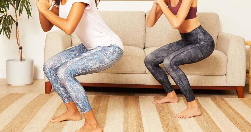 two women in workout outfits doing squats inside a living room