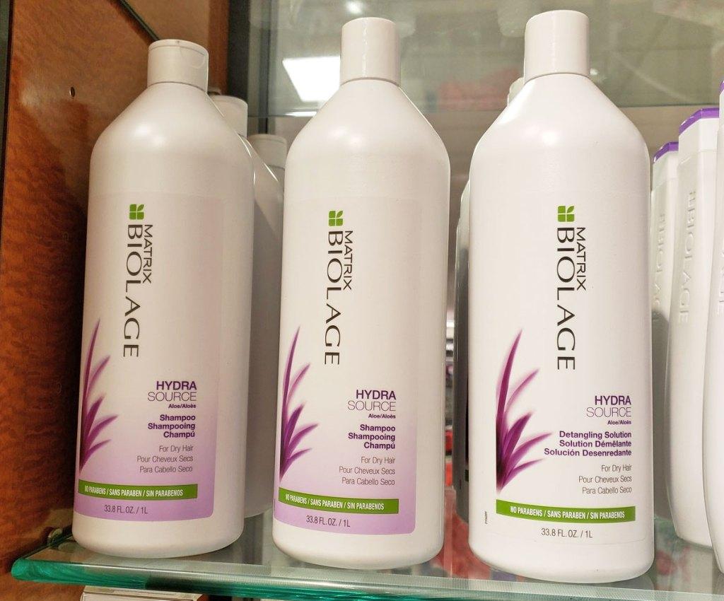large bottles of matrix biolage shampoo and conditioner on glass display shelf