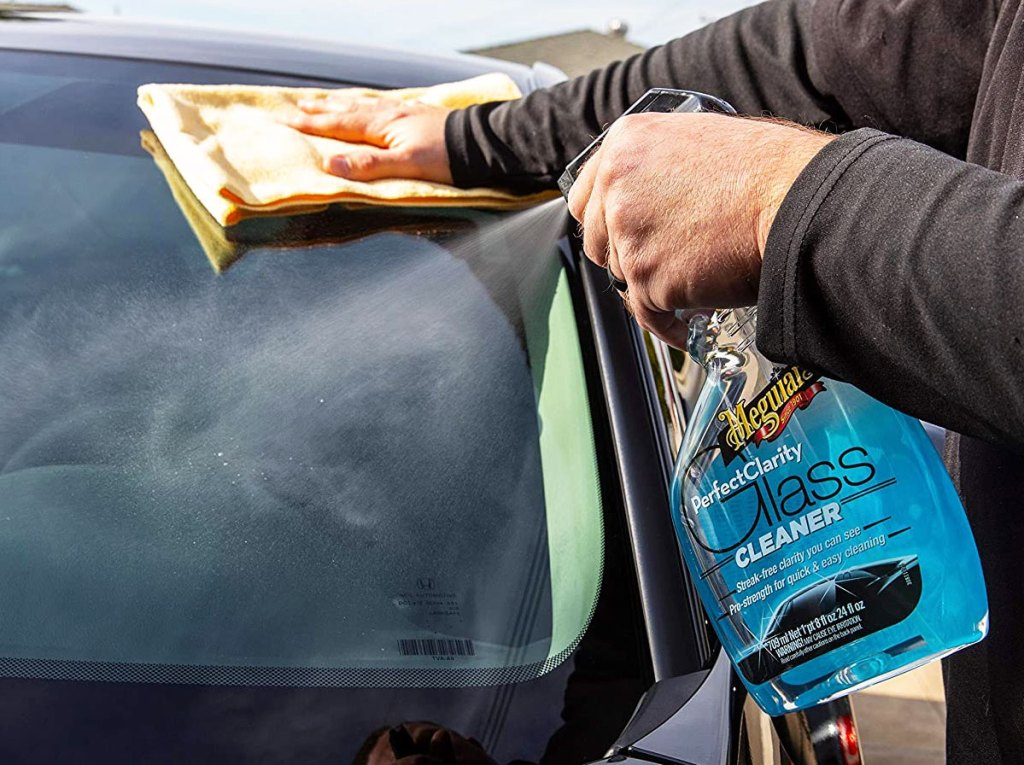 person spraying glass cleaner on windshield of car and wiping with yellow cloth