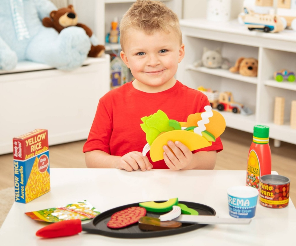 boy sitting at table playing with taco playset