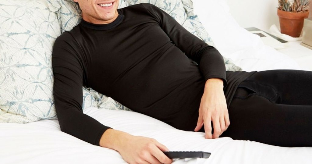 man laying on a bed wearing black thermal underwear set