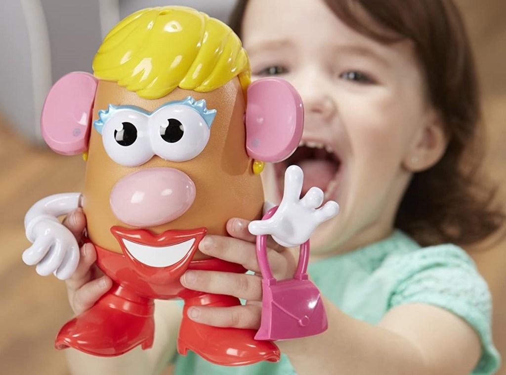 girl holding a Mrs Potato Head toy