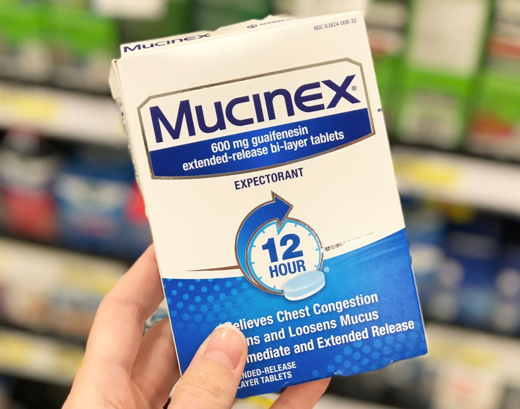 person holding up blue and white box of Mucinex Chest Congestion