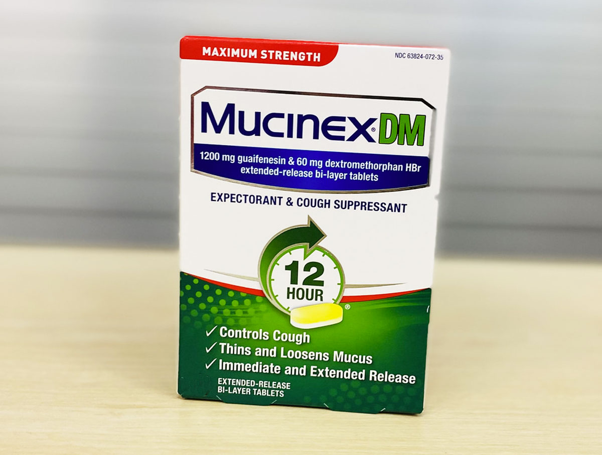 green and white box of Mucinex DM Cough Suppressant tablets