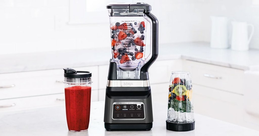 ninja blender with fruit inside on a kitchen counter with two individual blender cups next to it