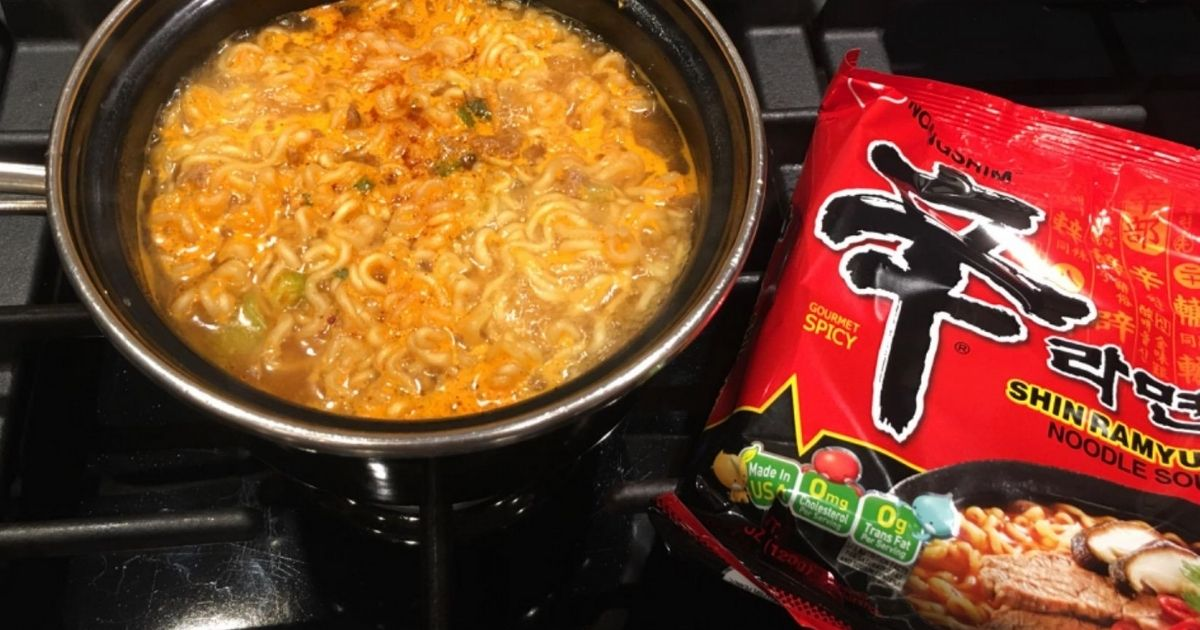 noodle soup cooking on a stovetop in a pot next to the soup packaging