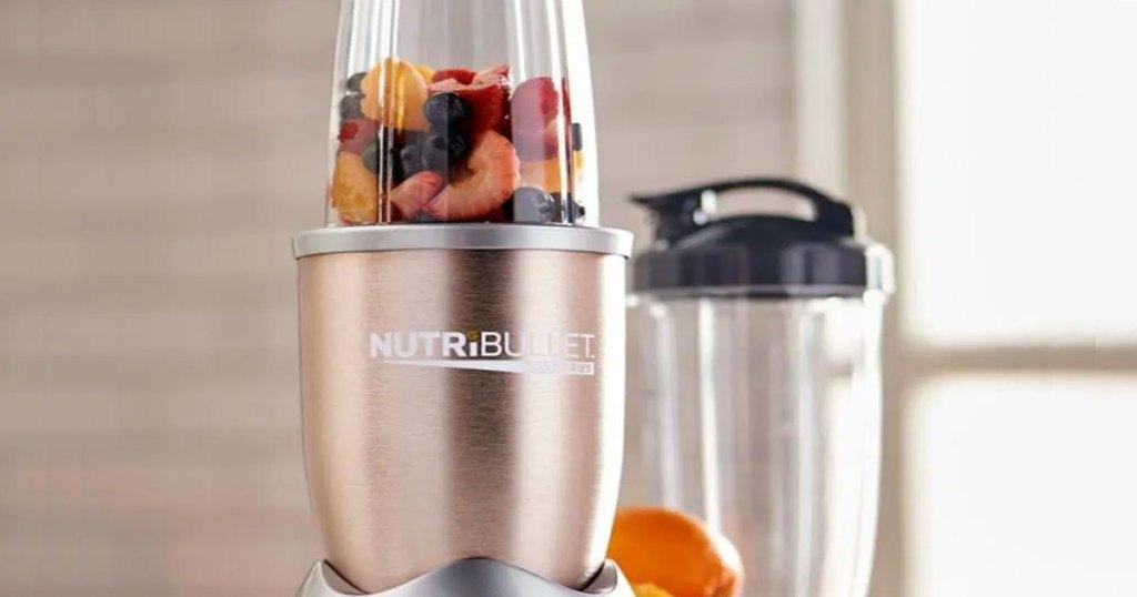 gold nutribullet blender with fruit inside and extra blending cup in background