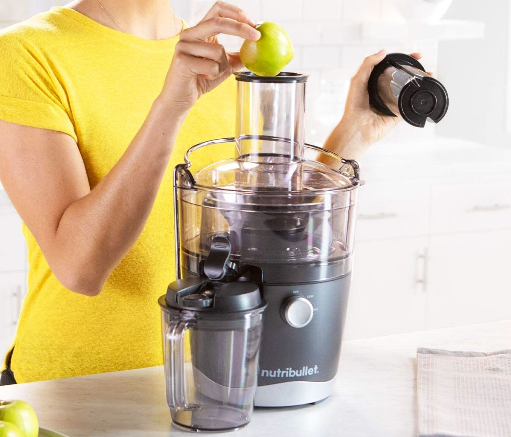 woman in yellow shirt using a nutribullet juicer
