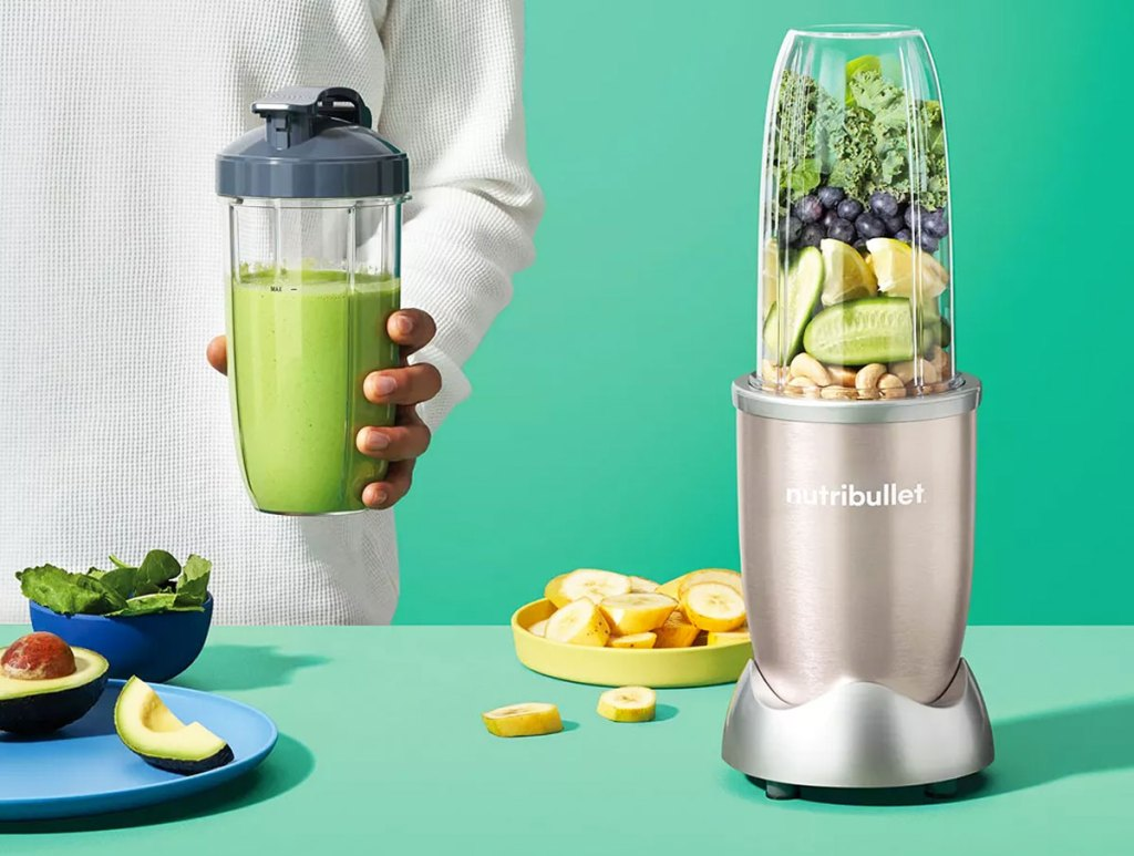 woman holding a smoothie blending cup next to a gold nutribullet blender