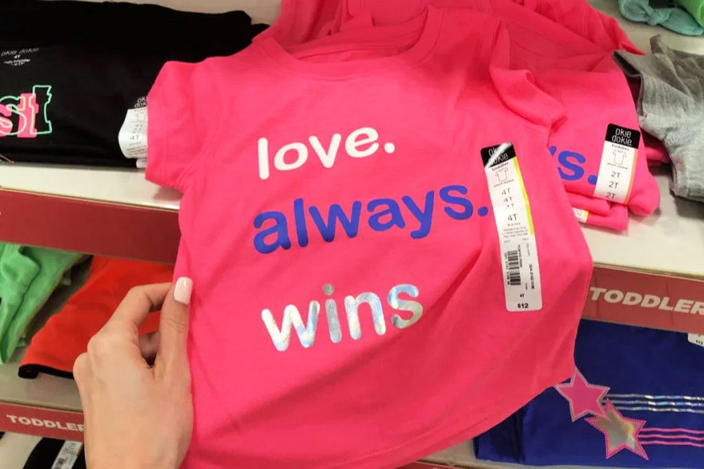 person holding pink toddler shirt that says love always wins