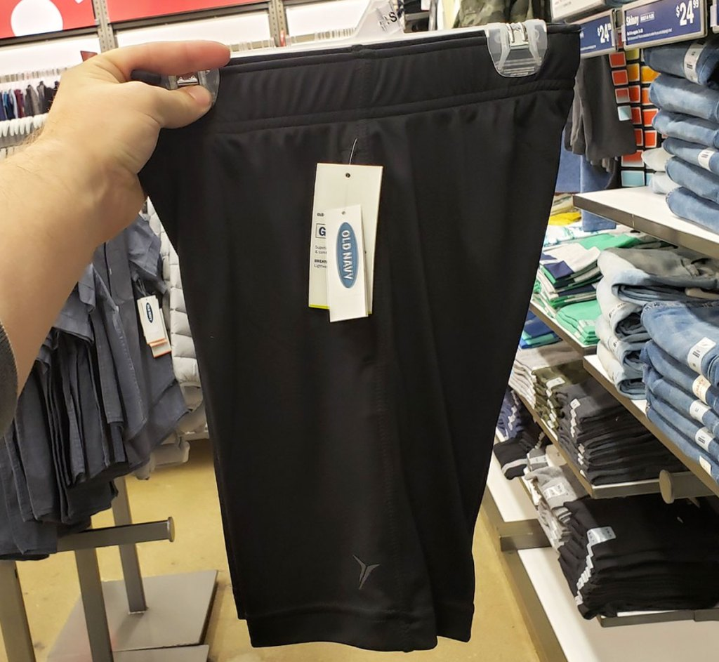 person holding up pair of men's black active shorts
