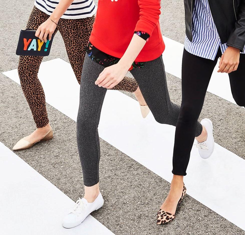 three women wearing leggings walking across the street