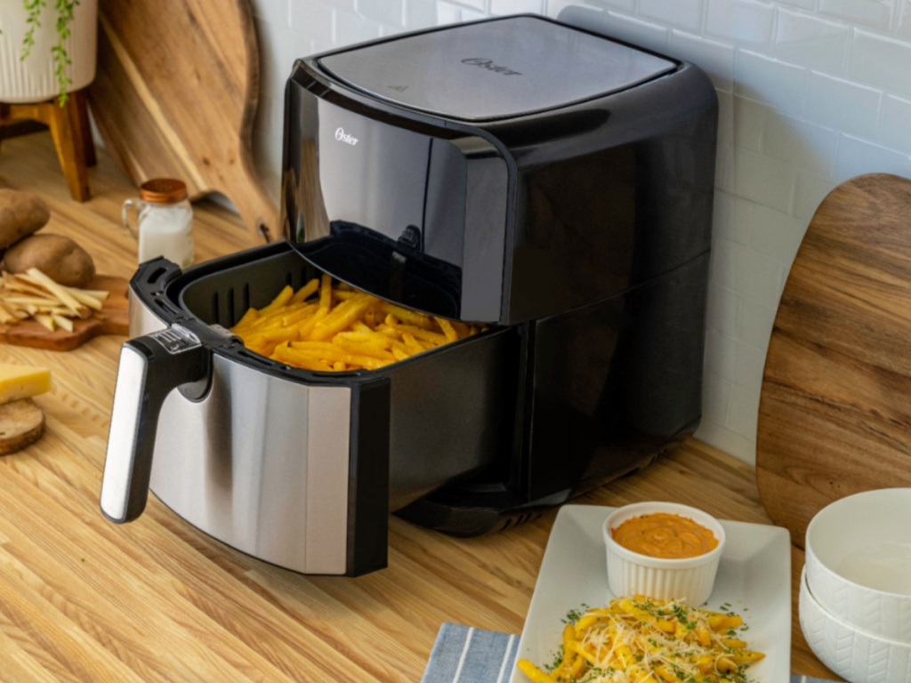 Oster DiamondForce XL Air Fryer sitting on a kitchen counter with french fries in the basket