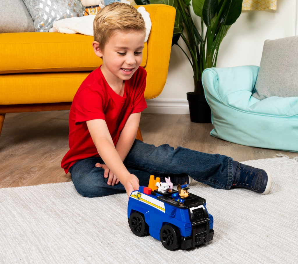 boy playing PAW Patrol Chase's Ride 'n' Rescue Transforming 2-in-1 Playset and Police Cruiser