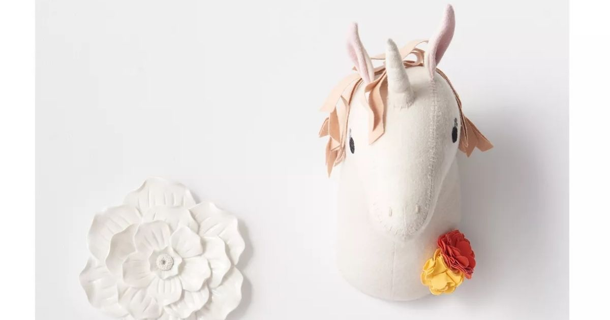 plush unicorn head and flower decor mounted on a white wall