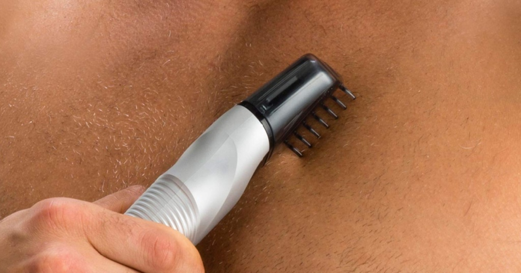 man holding a body trimmer close to his chest