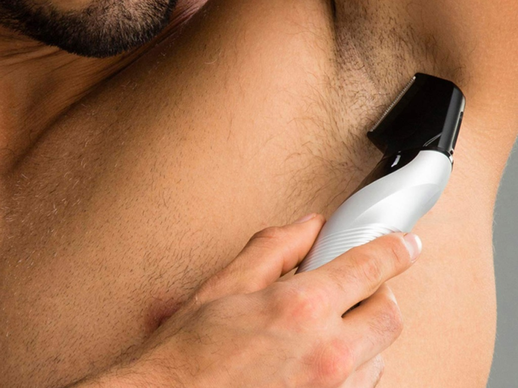 man holding a a body trimmer up to his underarm