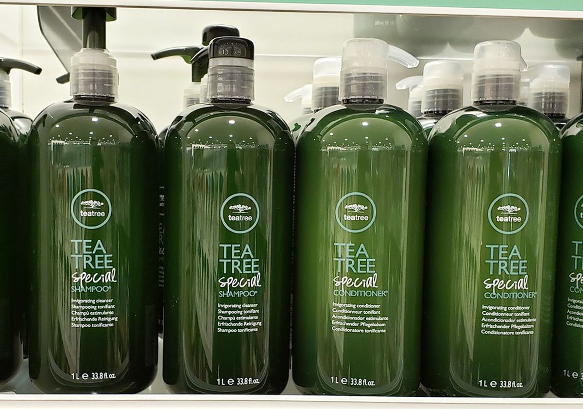large green bottles of tea tree shampoo and conditioner on display shelf
