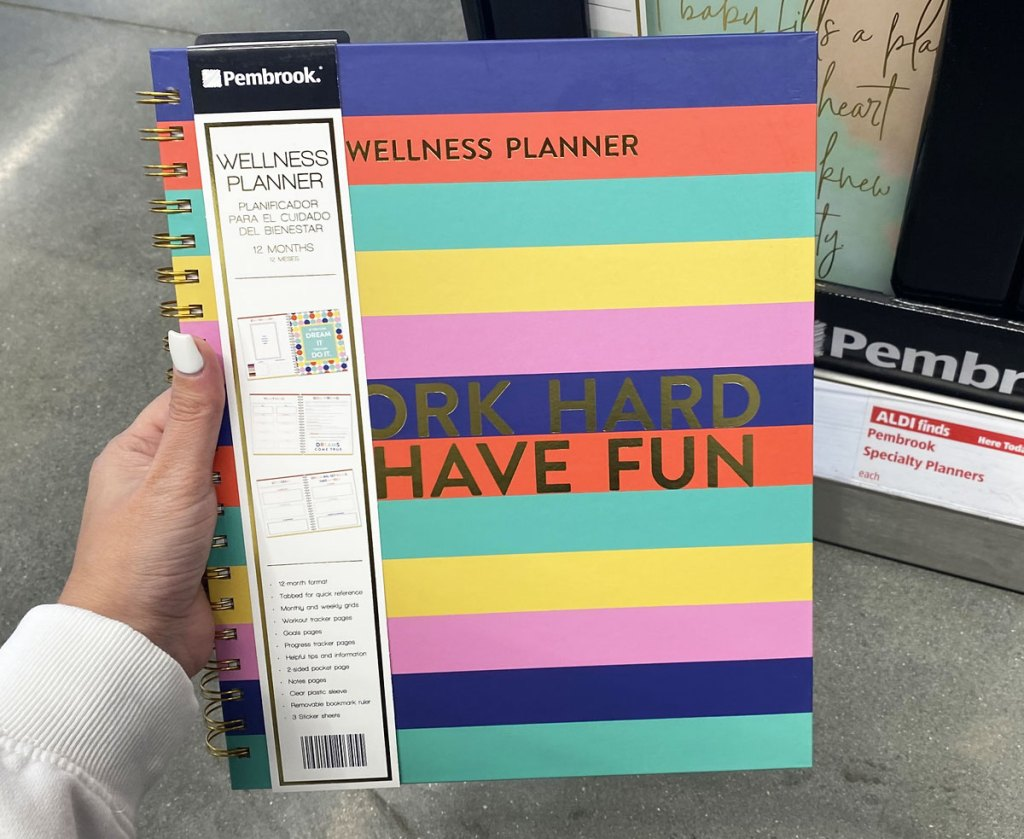 woman holding up multi-color striped 12-month wellness planner