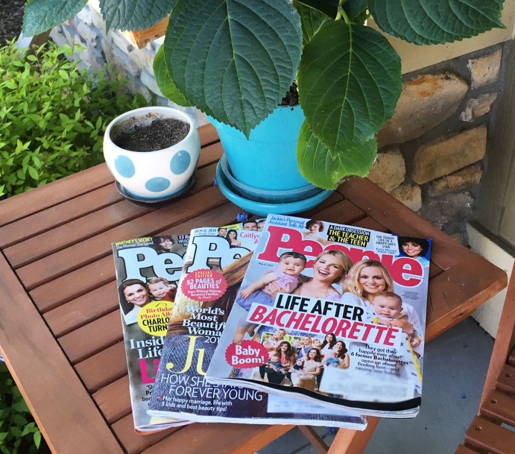 three issues of people magazine laid out on wood patio side table