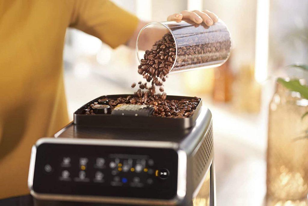 person pouring espresso beans in top of phillips espresso machine
