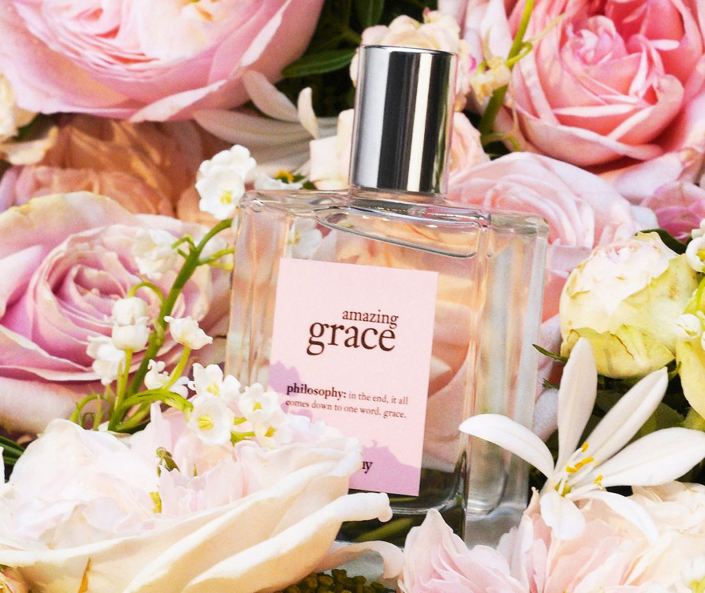 bottle of amazing grace perfume in a bouquet of pink flowers