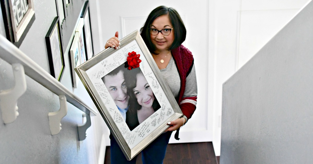 woman holding framed photo with bow