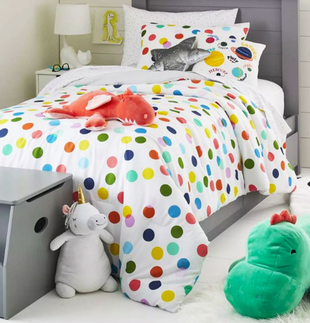 white comforter with multi-colored polka dot print on a kids bed