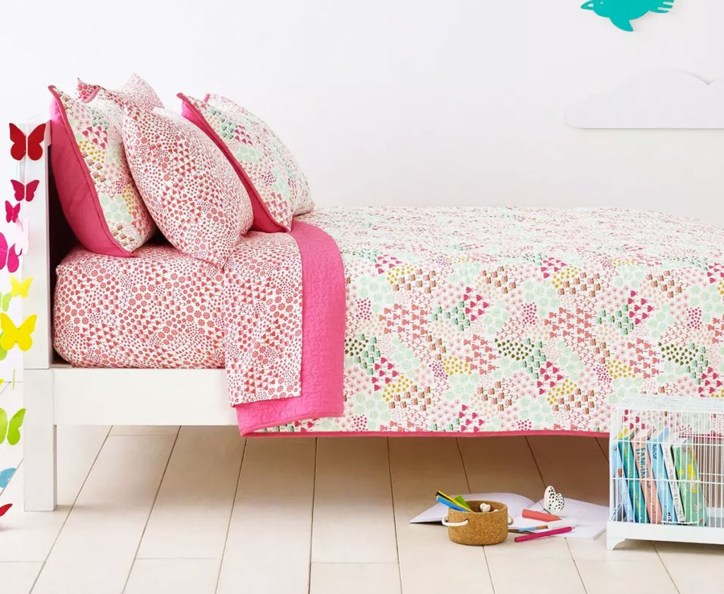 pink printed quilt on a kids bed