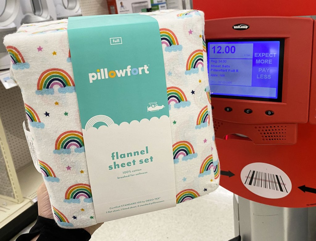 person holding up a set of rainbow print pillowfort flannel sheets next to a red target price scanner