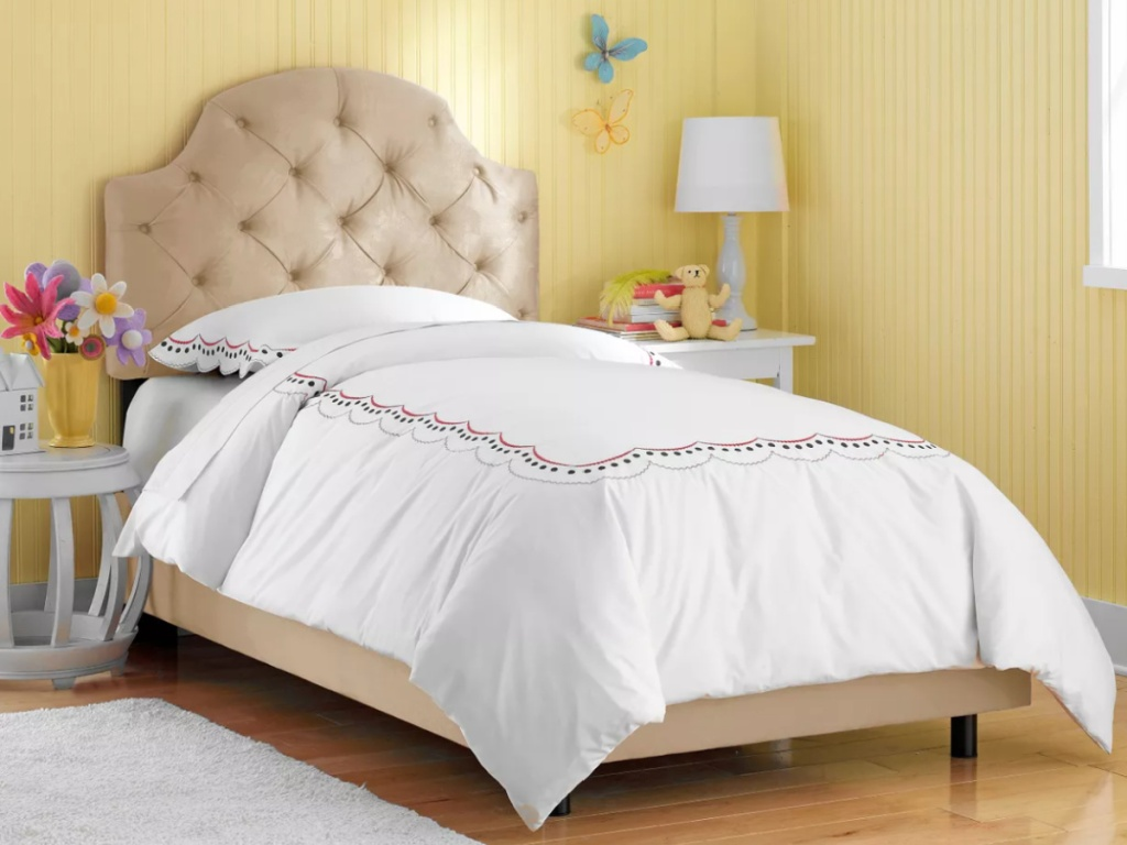 tan twin bed with tufted headboard in a yellow bedroom
