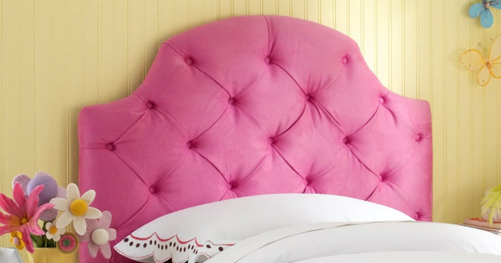 bright pink tufted kids headboard in a yellow bedroom