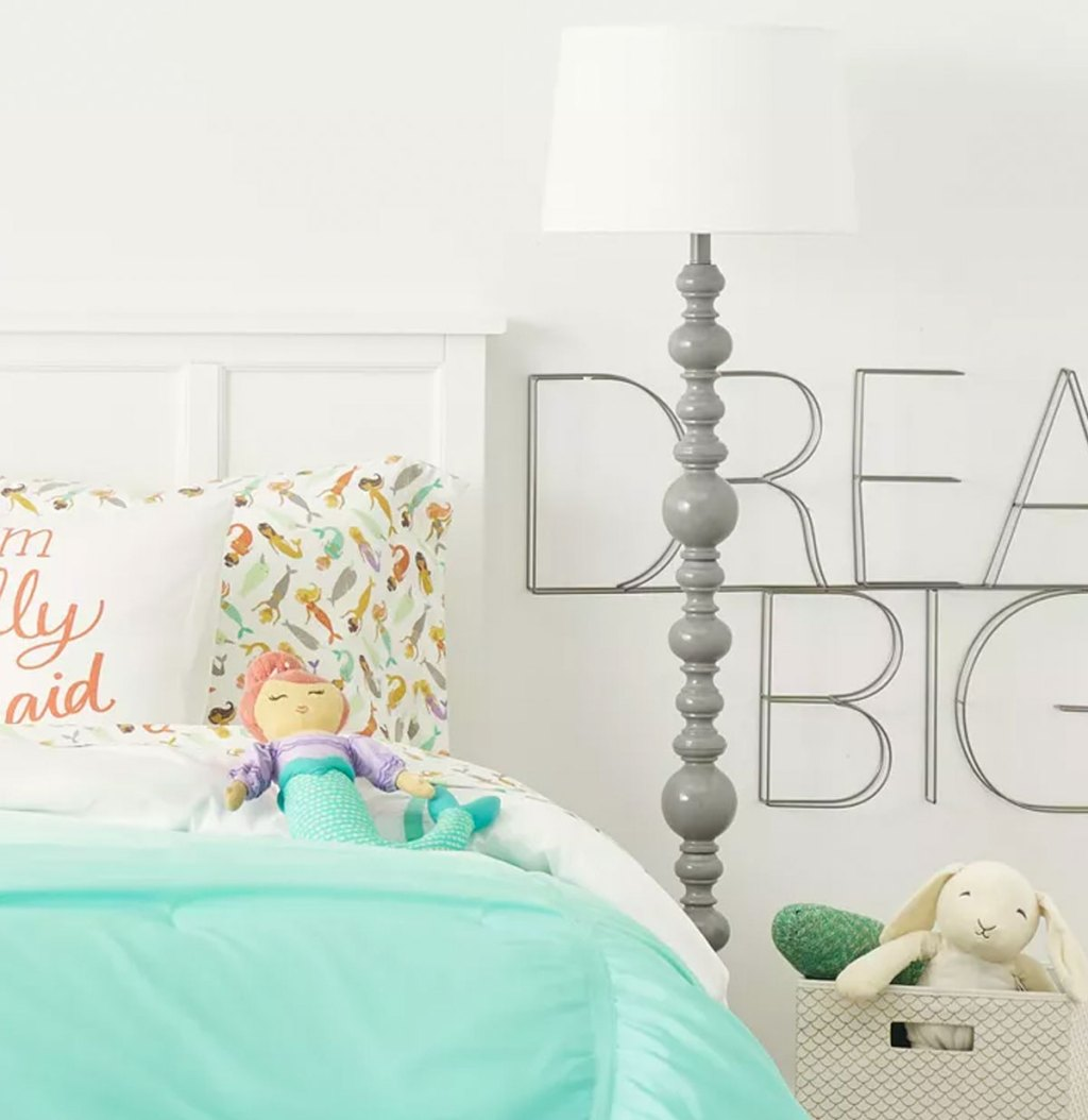 grey floor lamp next to bright blue comforter on bed