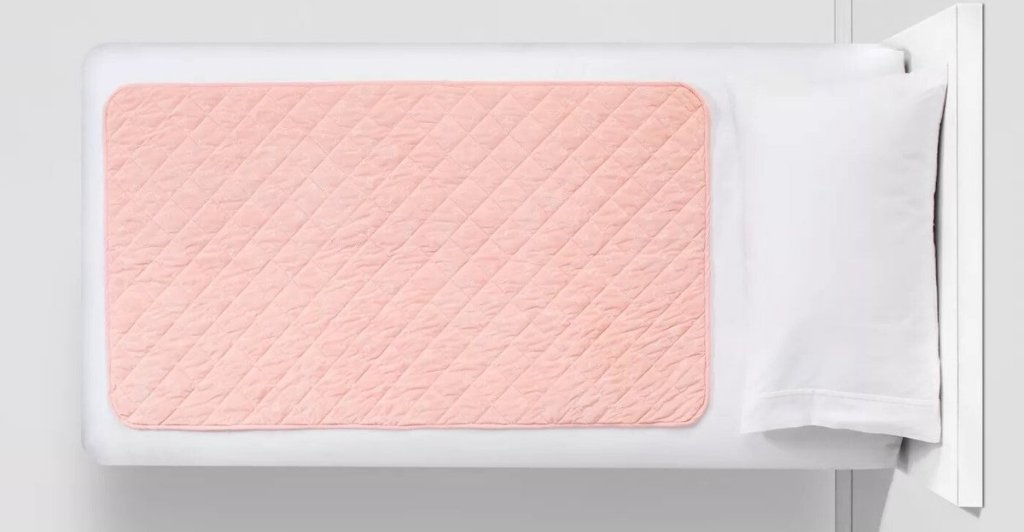pink colored Pillowfort Waterproof Sleep Anywhere Pad on white bed