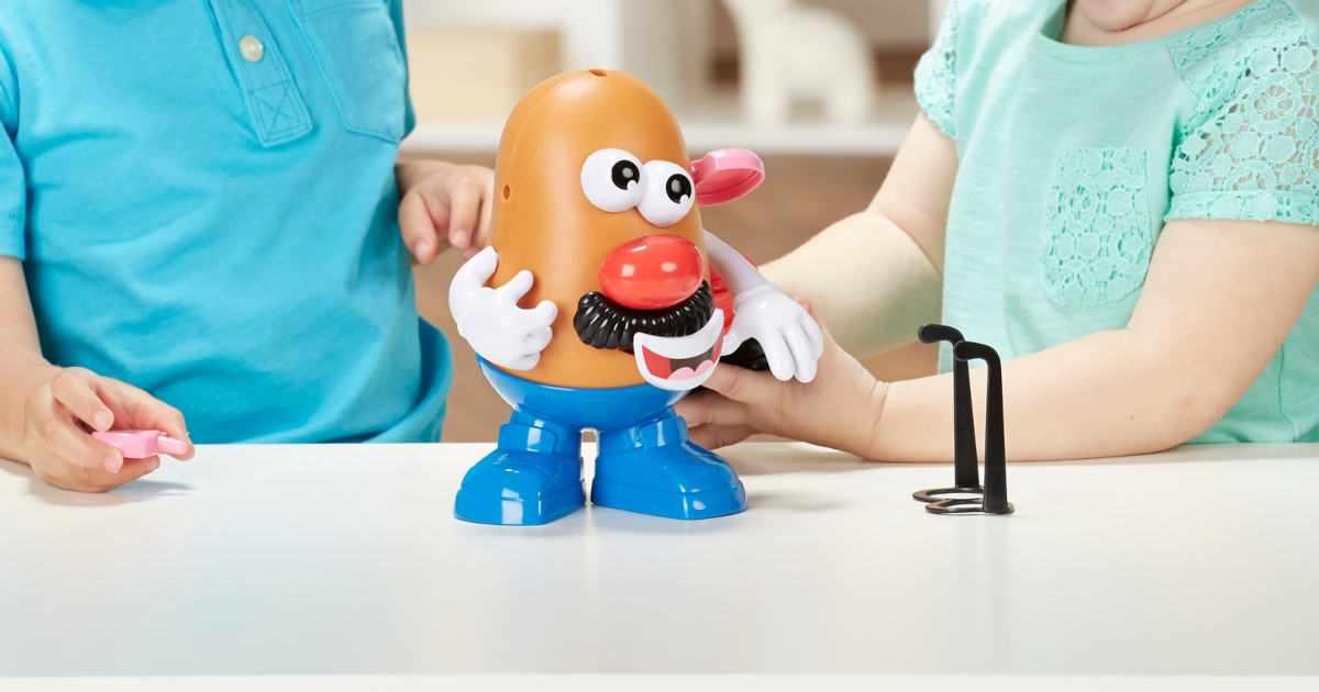 Mr. Potato Head on a table with one kid on each side playing