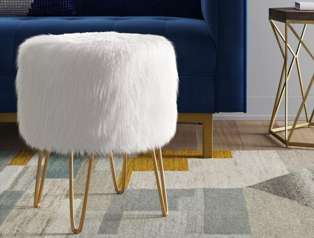 white furry ottoman with gold legs