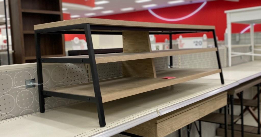 wood and metal tv stand on shelf