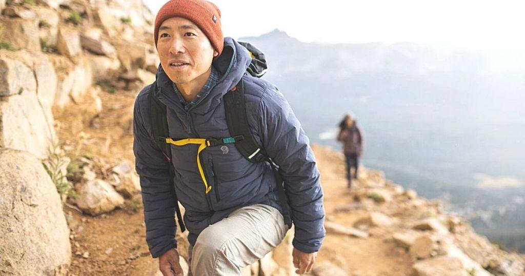 man hiking mountain wearing blue puffer coat
