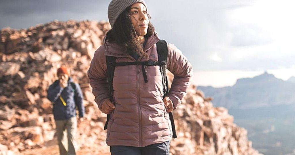 woman hiking a mountain wearing puffer coat