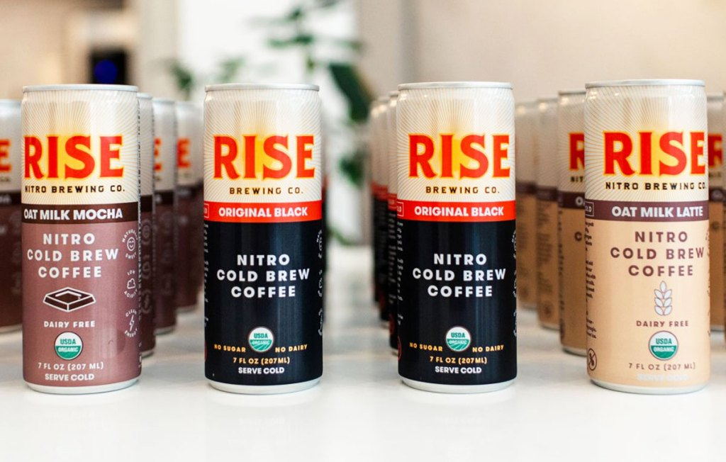 various flavors of rise cold brew coffee cans lined up on table