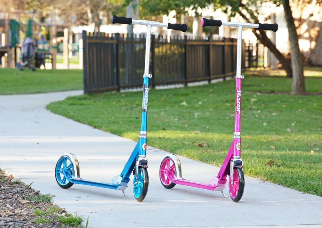 blue and pink scooters on pathway at a park