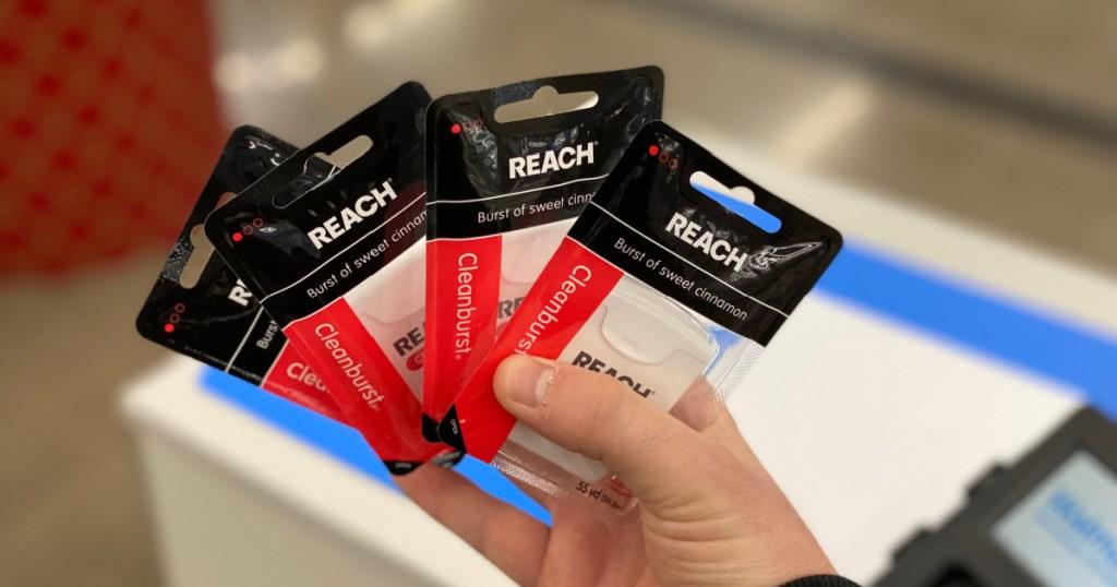 hand holding 4 packs of Reach Dental Floss Cleanburst