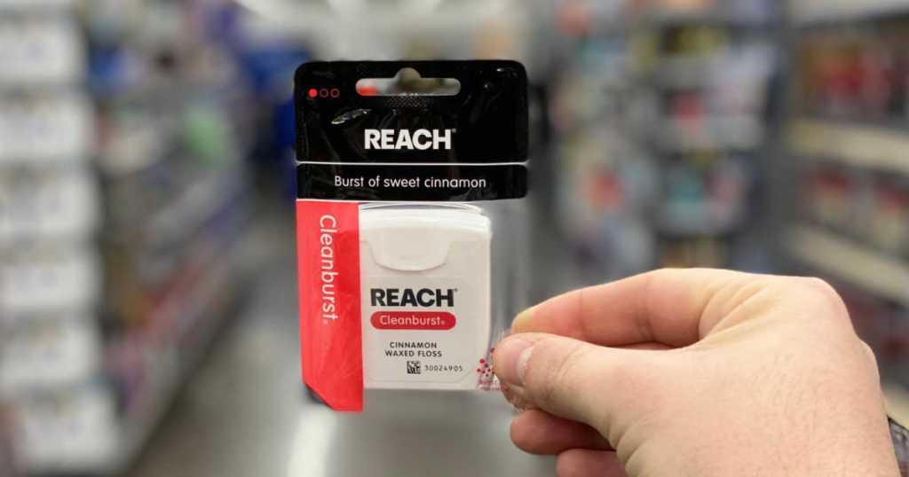 hand holding pack of Reach Dental Floss Cleanburst