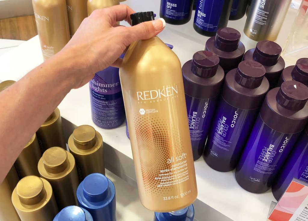 person holding up gold bottle of redken conditioner
