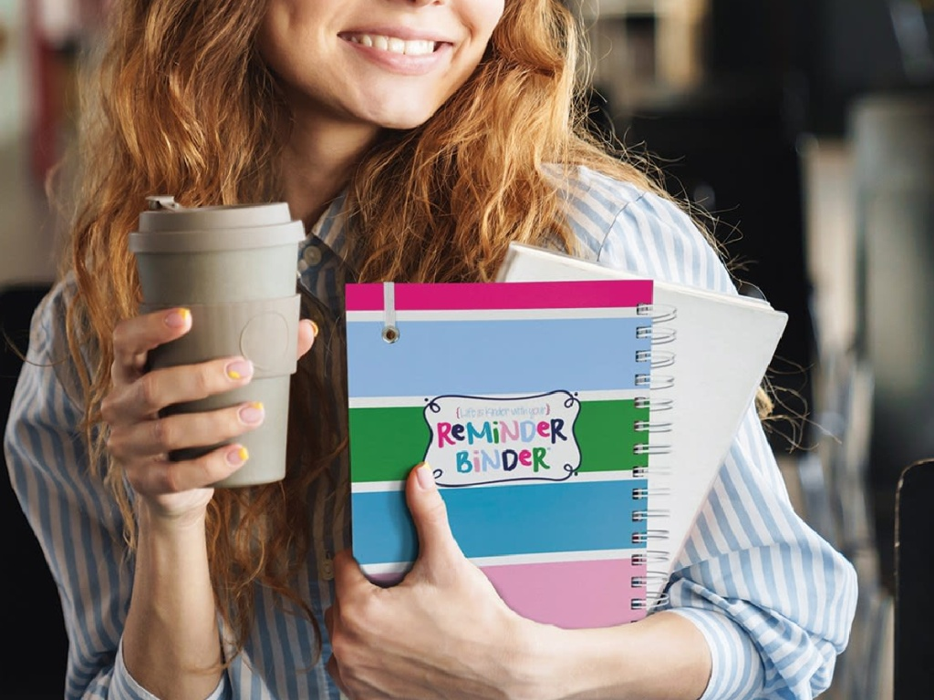 Woman in a coffee shop holding a coffee and a planner