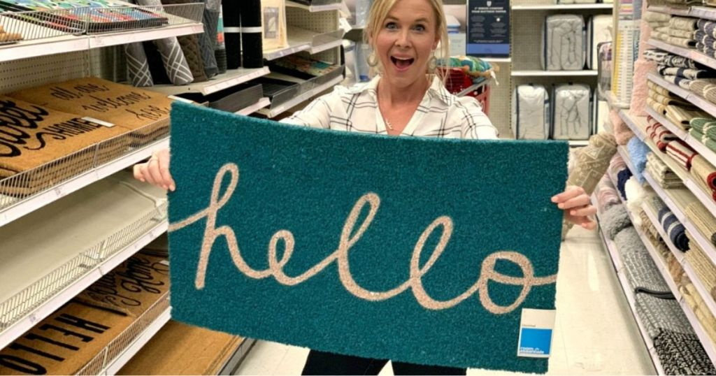 Woman holding up doormat that says hello