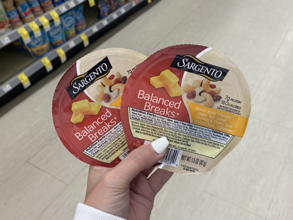 manicured hand holding 2 sargento balanced breaks at walgreens